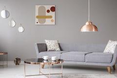 Kopparlamp- och kaffetabell framme av en modern soffa i en grå vardagsruminre arkivfoto