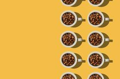 Koppbegrepp Vitkoppar med kaffebönor på gul bakgrund Fotografering för Bildbyråer