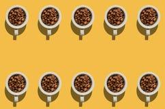 Koppbegrepp Vitkoppar med kaffebönor på gul bakgrund Royaltyfri Foto