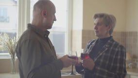 Koppelen de bejaarden aan wijnglazen die zich door het brede venster in de keuken bevinden Familieverhoudingen stock footage