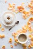 Koppen av coffe och en munk på vit texturerade bakgrund arkivbild