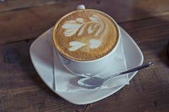 Koppen av espressolatte med mjölkar blomman Arkivfoto