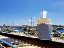 Koppen av glass med tomt utrymme står på en veranda mot bakgrunden av en port royaltyfria bilder