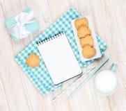 Koppen av mjölkar, den hjärta formade kakor, gåvaasken och notepaden Arkivfoton