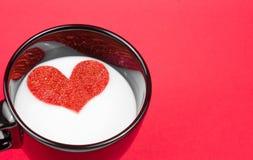 Koppen av mjölkar med dekorativ hjärta på röd bakgrund, begrepp av valentindagen Royaltyfri Foto