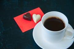 Koppen av stark kaffe och hjärta formade mörka och vita choklader Arkivfoto