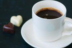 Koppen av stark kaffe och hjärta formade mörka och vita choklader Arkivfoton