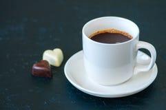 Koppen av stark kaffe och hjärta formade mörka och vita choklader Royaltyfria Foton