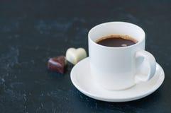 Koppen av stark kaffe och hjärta formade mörka och vita choklader Royaltyfria Bilder