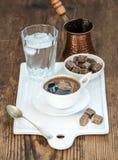 Koppen av svart kaffe, kopparkrukan, vatten med is i exponeringsglas och kuber för rottingsocker på den vita keramiska portionen  Royaltyfri Bild