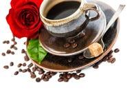 Koppen av svart kaffe och den röda rosen blommar över vit Royaltyfri Bild
