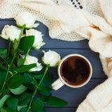 Koppen av svart kaffe, vit stack plädet och vita rosor, på dar Arkivbilder