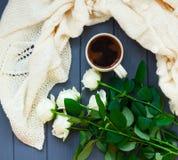 Koppen av svart kaffe, vit stack plädet och vita rosor, på dar Arkivfoton