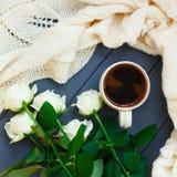 Koppen av svart kaffe, vit stack plädet och vita rosor, på dar Arkivbild