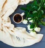 Koppen av svart kaffe, vit stack plädet och vita rosor, på dar Royaltyfria Bilder