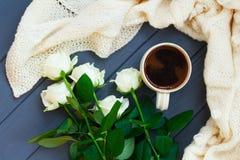 Koppen av svart kaffe, vit stack plädet och vita rosor, på dar Fotografering för Bildbyråer