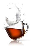 Koppen av svart te med mjölkar färgstänk Royaltyfri Fotografi