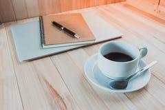 Koppen av svart varm coffec satte nära den digitala anteckningsboken Arkivfoto