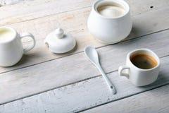 Koppen av varm kaffeespresso, kaffebönor, tillbringare av mjölkar och bowlar med socker på vit bakgrund för kopieringsutrymme Kaf arkivfoton