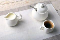 Koppen av varm kaffeespresso, kaffebönor, tillbringare av mjölkar och bowlar med socker på vit bakgrund för kopieringsutrymme Kaf arkivbilder