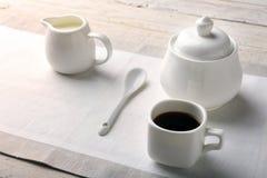 Koppen av varm kaffeespresso, kaffebönor, tillbringare av mjölkar och bowlar med socker på vit bakgrund för kopieringsutrymme Kaf fotografering för bildbyråer
