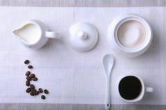Koppen av varm kaffeespresso, kaffebönor, tillbringare av mjölkar och bowlar med socker på vit bakgrund för kopieringsutrymme Kaf royaltyfri bild