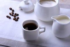 Koppen av varm kaffeespresso, kaffebönor, tillbringare av mjölkar och bowlar med socker på vit bakgrund för kopieringsutrymme Kaf royaltyfri fotografi