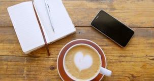 Koppen av varm kaffelatte med hjärta formade skumkonst med dagboken och mobiltelefonen 4k arkivfilmer