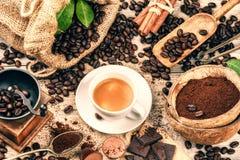 Koppen av varmt svart kaffe med gammalt trä maler molar och säckväv royaltyfri foto