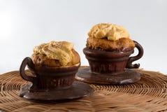 Koppen bakar ihop som koppar och tefat med choklad Arkivfoton