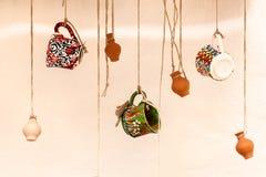 Koppen en kleipotten die op de kabels, het ontwerp en het binnenland hangen Royalty-vrije Stock Fotografie