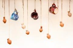 Koppen en kleipotten die op de kabels, het ontwerp en het binnenland hangen Stock Afbeeldingen