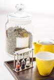 Koppen en theepot met horloges en losse thee in een container op witte achtergrond, product voor tearoom op houten plaat worden g Stock Foto's