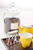 Koppen en theepot met horloges en losse thee in een container op witte achtergrond, product voor tearoom op houten plaat worden g Stock Afbeelding