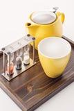 Koppen en theepot met horloges en losse thee in een container op witte achtergrond, product voor tearoom worden geplaatst die Royalty-vrije Stock Afbeelding