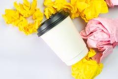 Koppen för tagandet för vitt kaffe klumpa ihop sig den bort med färgglat smulat papper på vit bakgrund royaltyfri bild