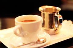 Koppen för varm choklad och en krus av mjölkar med ett socker i en parisisk restaurang royaltyfria bilder