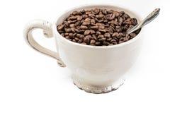 Koppen fyllde med kaffebönor som isolerades på vit Royaltyfria Foton
