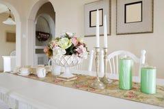 Koppen, kaarsen, en bloemen op een lijst royalty-vrije stock afbeelding