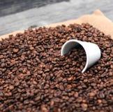 Koppen kaffe fyllde med kaffebönor mot träbakgrund Arkivfoton