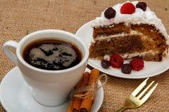 Koppen kaffe, kanel, gaffeln och skivan av den ljusbruna kakan dekorerar Arkivbilder