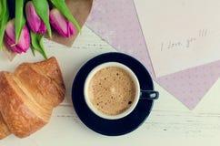 Koppen kaffe med buketten av rosa tulpan och anmärkningar ÄLSKAR JAG DIG Arkivfoton
