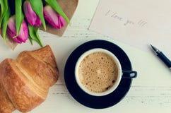 Koppen kaffe med buketten av rosa tulpan och anmärkningar ÄLSKAR JAG DIG Royaltyfri Foto