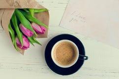 Koppen kaffe med buketten av rosa tulpan och anmärkningar ÄLSKAR JAG DIG Fotografering för Bildbyråer