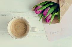 Koppen kaffe med buketten av rosa tulpan och anmärkningar ÄLSKAR JAG DIG Royaltyfri Bild