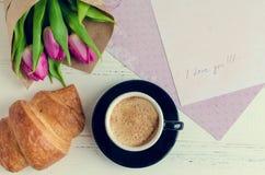 Koppen kaffe med buketten av rosa tulpan och anmärkningar ÄLSKAR JAG DIG Arkivbilder