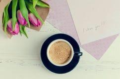 Koppen kaffe med buketten av rosa tulpan och anmärkningar ÄLSKAR JAG DIG Royaltyfri Fotografi