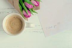 Koppen kaffe med buketten av rosa tulpan och anmärkningar ÄLSKAR JAG DIG Royaltyfria Bilder
