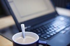 Koppen kaffe med en tesked stämplade med en kaffelogo i fokus med en bärbar dator ut ur focusin bakgrunden Royaltyfri Fotografi