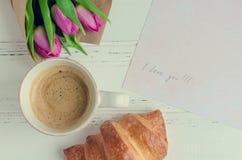 Koppen kaffe med gifflet, buketten av rosa tulpan och anmärkningar ÄLSKAR JAG DIG Royaltyfria Bilder